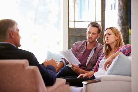 advice: Couple At Home Meeting With Financial Advisor