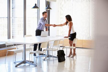 interview job: El hombre de negocios dando la mano a un solicitante de empleo
