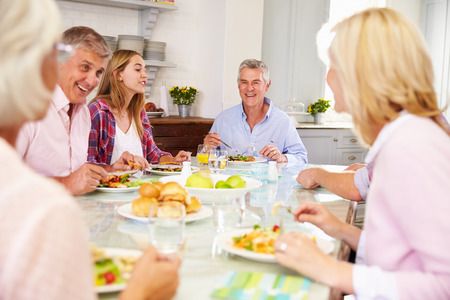 adult offspring: Group Of Friends Enjoying Meal At Home Together