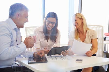 oficina: Grupo de compañeros reunidos alrededor de una mesa en una oficina