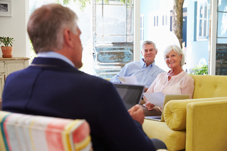 financial advisor: Senior Couple At Home Meeting With Financial Advisor Stock Photo