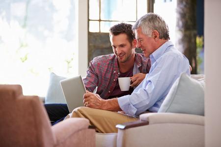 ayudando: Adultos Hijo ayuda al padre mayor con el ordenador en el hogar