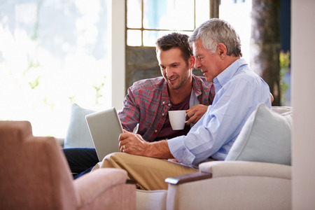 adult male: Son Adulto che aiuta anziano Padre Con computer a casa