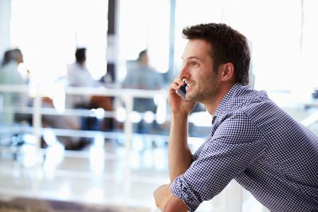 personas dialogando: Retrato de hombre hablando por teléfono, interior de la oficina