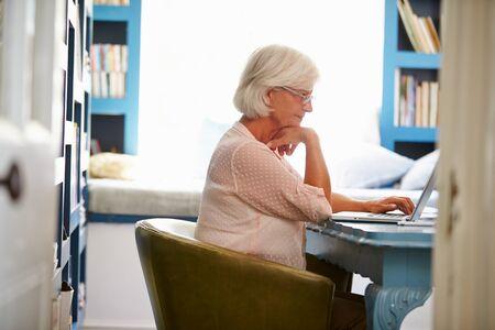 fila de personas: Mujer mayor en el escritorio de trabajo en Home Office con la computadora port�til