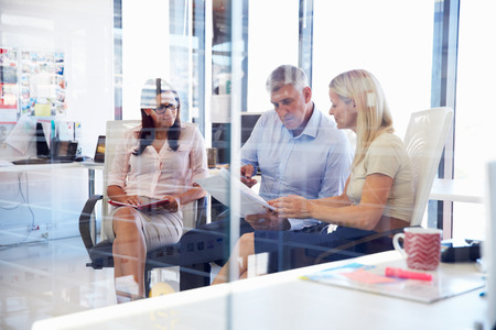 business executive: Group of colleagues talking in an office Stock Photo