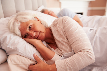 lying on bed: Worried Senior Woman Lying Awake In Bed Stock Photo