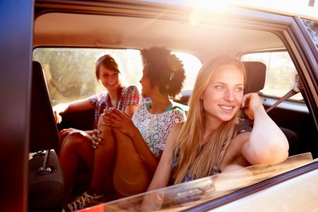 manejando: Tres mujeres sentado en el asiento trasero del coche en viajes por carretera