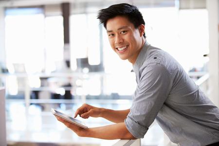 사무실에서 태블릿을 사용하는 젊은 남자의 초상 스톡 콘텐츠