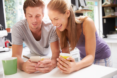 whilst: Couple Eating Breakfast Whilst Checking Mobile Phone Stock Photo