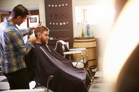 small business owner: Male Barber Giving Client Haircut In Shop