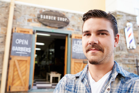 shop owner: Portrait Of Hipster Barber Standing Outside Shop Stock Photo