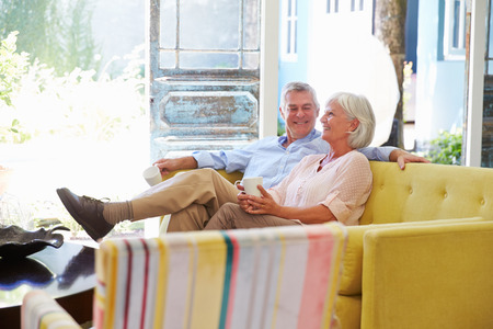 couple relaxing: Senior Couple At Home Relaxing In Lounge With Hot Drink Stock Photo