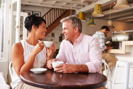 mixed race woman: Middle aged people meeting in a cafe