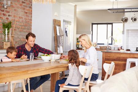 familia cenando: Familia que dice tolerancia antes de la cena Foto de archivo