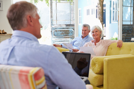 home planning: Senior Couple At Home Meeting With Financial Advisor Stock Photo