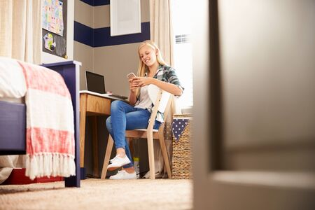 distraction: Girl sitting at a desk in her bedroom using smart phone