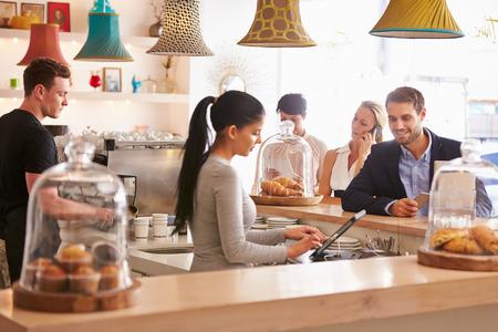 meseros: Ordenamiento Joven en el mostrador en un café