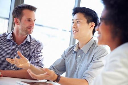 comunicação: Três profissionais de negócios que trabalham juntos Banco de Imagens