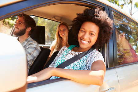 passenger car: Group Of Friends In Car On Road Trip Together Stock Photo