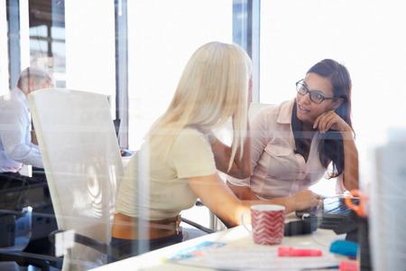 mujer trabajadora: Los compa�eros de trabajo de las mujeres que hablan en una oficina Foto de archivo