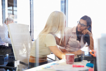 corporate business: Women coworkers talking in an office Stock Photo