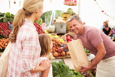 농부 시장 마구간에 신선한 야채를 사는 가족