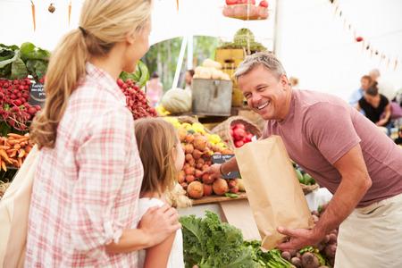 Familie Koop Verse Groenten Op Boerenmarkt Stall Stockfoto