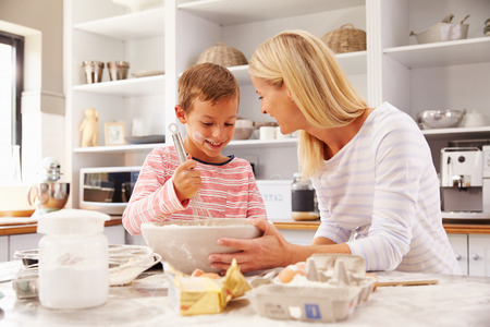young mother: Mother and son baking together at home