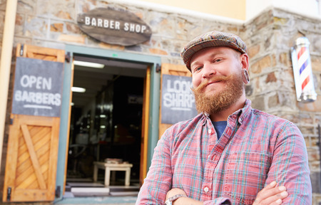 hairdressers: Portrait Of Hipster Barber Standing Outside Shop Stock Photo