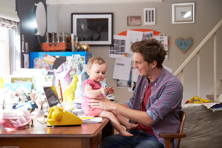 Father With Daughter Running Small Business From Home Office