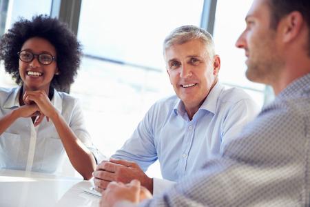 personas escuchando: Tres profesionales de negocios trabajando juntos