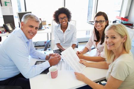 reunion de personas: Cuatro colegas reunidos alrededor de una mesa en una oficina