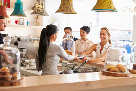 serving: Woman paying for her order in a cafe Stock Photo