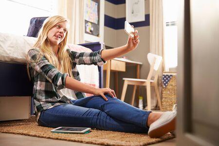 Girl taking selfie in her bedroom photo