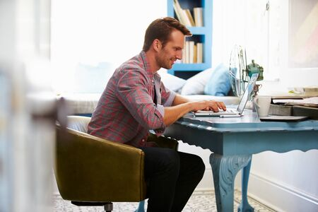 email security: Man At Desk Working In Home Office With Laptop Stock Photo