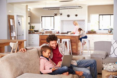Fadern använder dator med sonen, familjen i bakgrunden