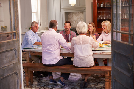 couple relaxing: Group Of Friends Enjoying Meal At Home Together