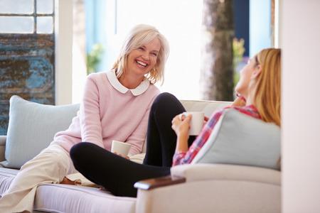 自宅のソファでリラックスした大人の娘と熟母 写真素材