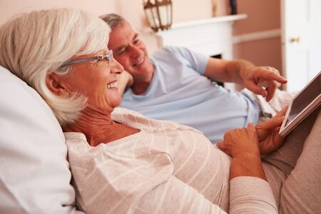 two people: Senior Couple Lying In Bed Looking At Digital Tablet