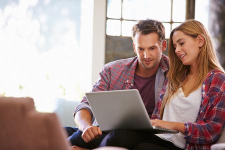 Couple à la maison dans Lounge Utiliser un ordinateur portable informatique