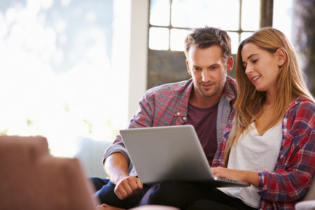 guy with laptop: Couple At Home In Lounge Using Laptop Computer Stock Photo