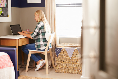 girl bedroom: Girl sitting at a desk in her bedroom using laptop