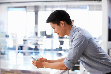 Retrato de hombre joven con teléfono inteligente en una oficina