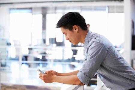 hombre pensando: Retrato de hombre joven con teléfono inteligente en una oficina