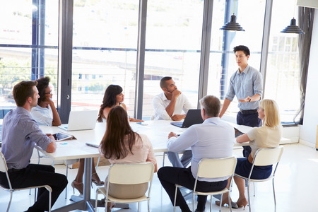 personnes: Homme d'affaires présentant à ses collègues lors d'une réunion