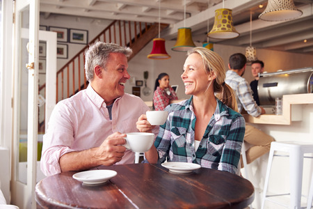 women holding cup: Couple meeting in a cafe Stock Photo