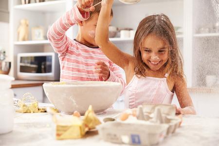 hombre cocinando: Dos niños que se divierten de hornear en la cocina