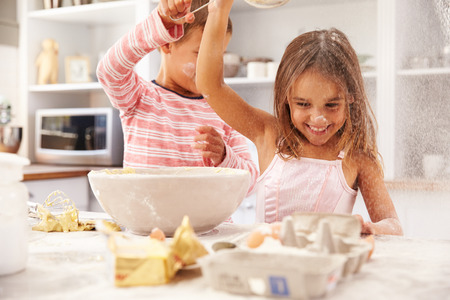 kids: Two children having fun baking in the kitchen Stock Photo