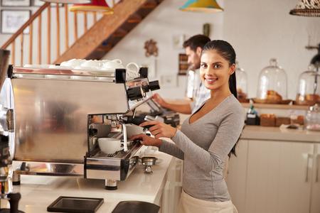 grinder machine: Female barista at work